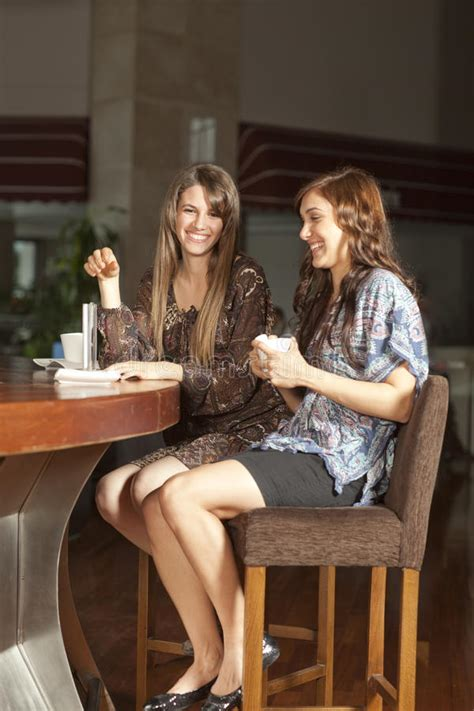 Two Young Women Drinking Coffee At A Bar Stock Photo